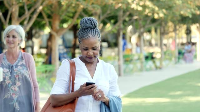 vídeos de stock e filmes b-roll de independent senior woman walks in city park - independência