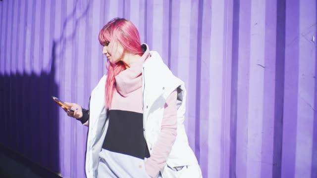 stockvideo's en b-roll-footage met onafhankelijke jonge vrouw met roze haar maakt gebruik van smartphone op paarse containers achtergrond. slow motion - roze haar