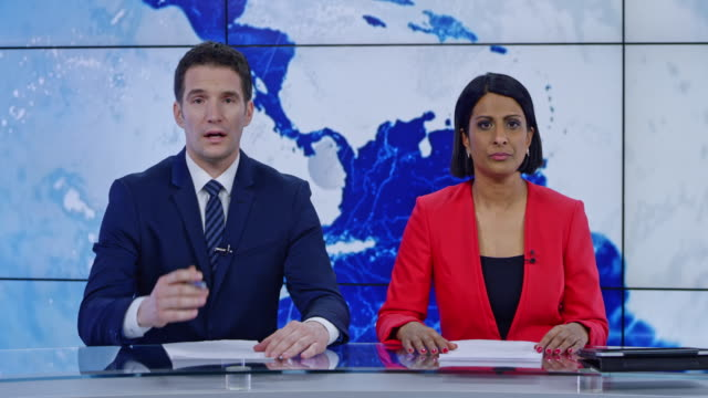 LD Indian anchorwoman and Caucasian anchorman presenting the news Wide locked down shot of an Indian female anchor and her Caucasian colleague presenting the latest news from around the world. Shot in Slovenia. journalist stock videos & royalty-free footage