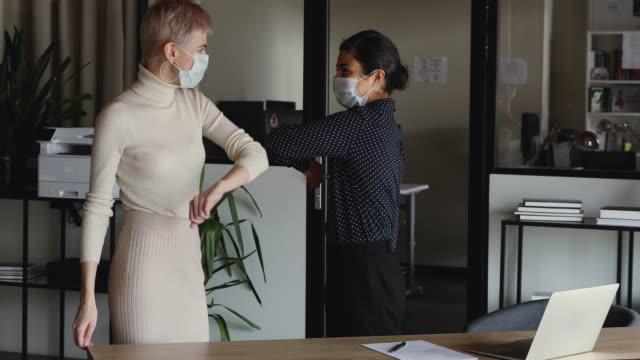 indiska och kaukasiska affärskvinnor bära masker hälsning med armbåge bump - office workers talking bildbanksvideor och videomaterial från bakom kulisserna