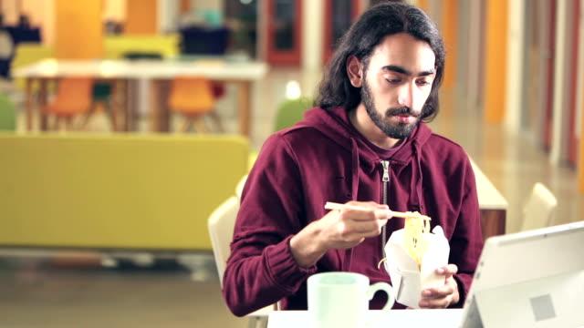 Hombre indio y el Cáucaso con la computadora, comiendo - vídeo