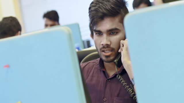 Indian businessman talking on landline phone at call center office Indian confident young businessman talking on landline phone at call center. Male entrepreneur is sitting at desk . landline phone stock videos & royalty-free footage