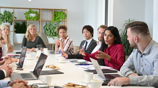 Indian businesswoman responding to colleague in meeting