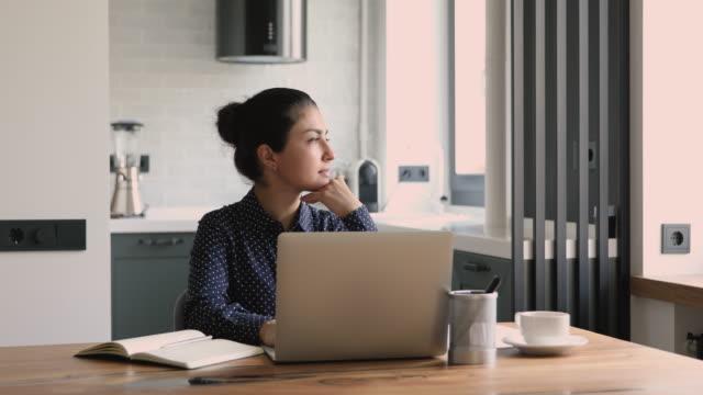 vídeos y material grabado en eventos de stock de empresaria india trabajar en portátil pensando en solución de problemas - posición descriptiva