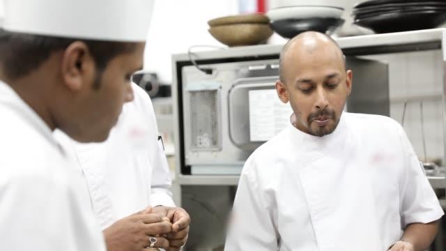 グルメレストランのプロのキッチンで調理するインドのシェフ - 料理人点の映像素材/bロール
