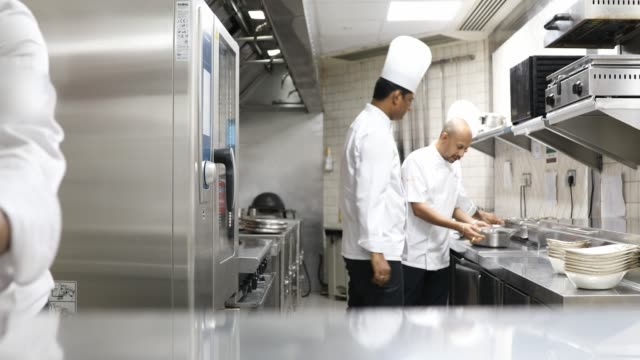 indian chefs cooking in a professional kitchen of a gourmet restaurant - busy restaurant kitchen stock videos & royalty-free footage