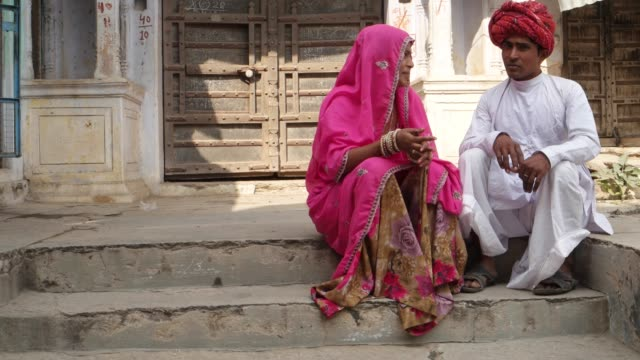 indian couple in front of old rajasthani architecture sitting and chatting - sari filmów i materiałów b-roll