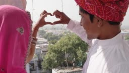 df5adcfc11 Indian Couple In Traditional Dress Make Heart Symbol With Fingers And Hand  Looking Down From A Vantage Point At Pushkar Mela Festival In Rajasthan  India ...