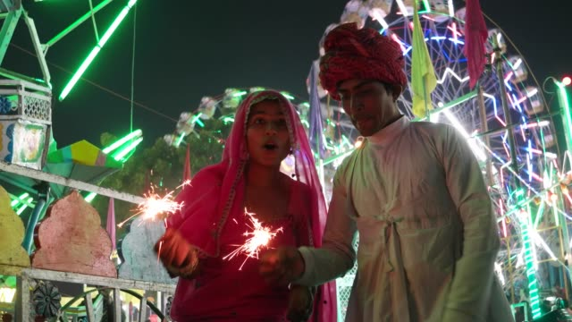 Indian couple in traditional dress with fire sparkle cracker at Diwali Mela festival in India video