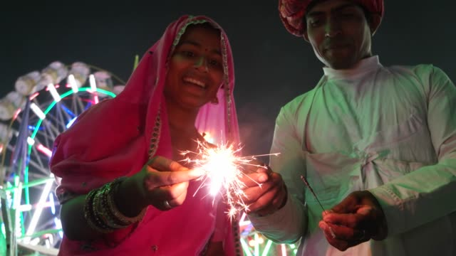 Indische Paare in Tracht mit Feuer Funkeln Cracker am Diwali Mela-fest in Indien – Video