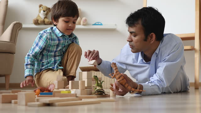 Indian dad and son play with dinosaurs toys and bricks