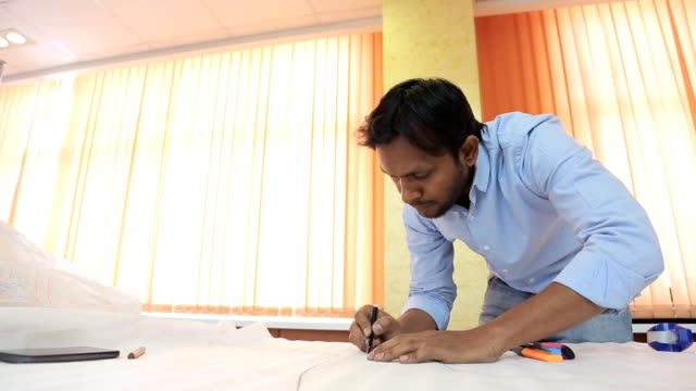 Indian engineer designer drafting draw on a table in a bright room video
