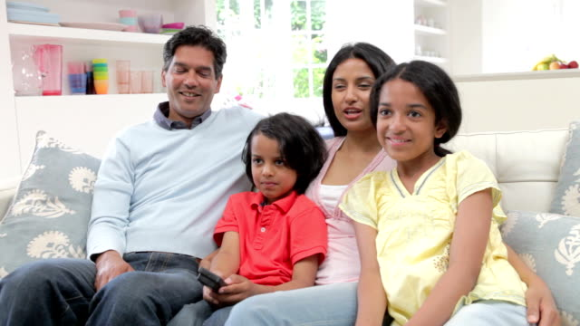 Indian Family Sitting On Sofa Watching TV Together Asian Indian family sitting on sofa together watching television.Shot on Canon 5d Mk2 with a frame rate of 25fps indian family stock videos & royalty-free footage