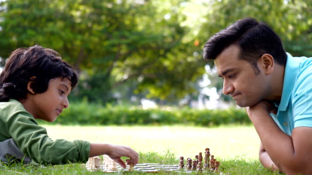 vídeos de stock e filmes b-roll de indian father and son playing chess while spending time together in a park - leisure time - xadrez