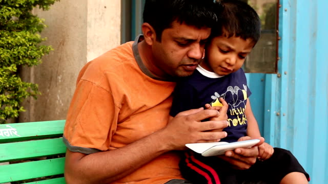 Indian father and son using smart phone video