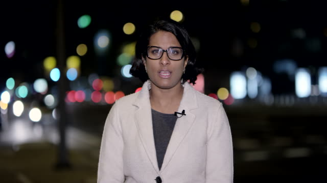 Indian female news reporter reporting live from the city center at night Wide handheld shot of a female Indian news reporter reporting to the studio from the city center at night. Shot in Slovenia. journalist stock videos & royalty-free footage