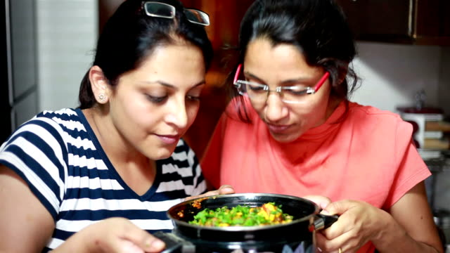 Indian housewives women smelling and appreciating food cooked by them Indian housewives women smelling and appreciating food cooked by them short length stock videos & royalty-free footage