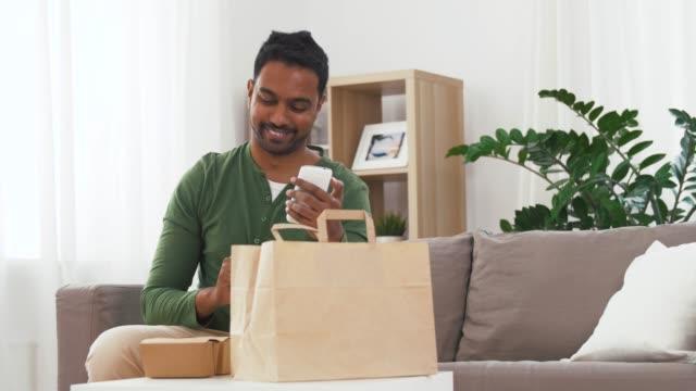 インド人男性が自宅で持ち帰り食品の注文をチェック - コントロール点の映像素材/bロール