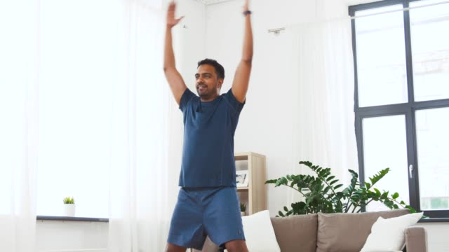 indian man doing jumping jack exercise at home - vídeo