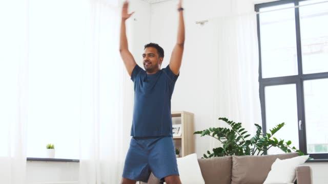 Indian man gör hoppning Jack Övning hemma video