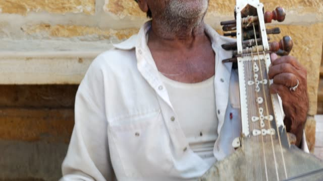 Indian Man plays traditional musical instrument in Jaisalmer Fort, Rajasthan, India video