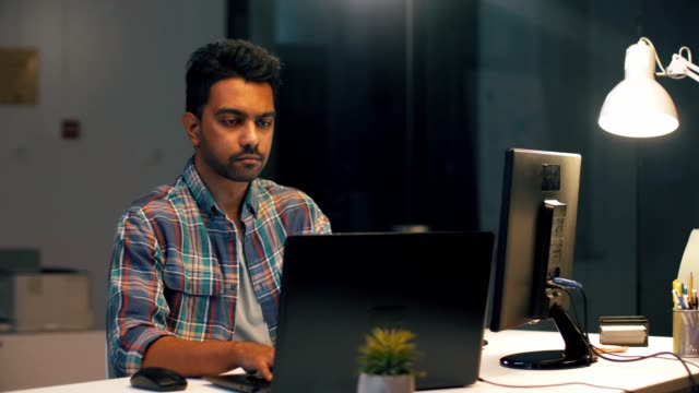 indian man with laptop working at night office - hindus filmów i materiałów b-roll