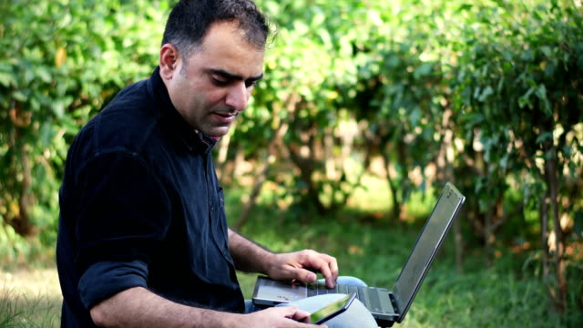 Indischer Mann arbeitet im öffentlichen Park auf einem Laptop im Freien – Video