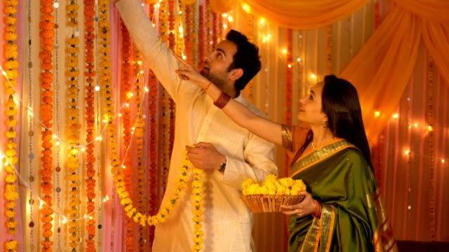 indisches ehepaar schmückt das haus mit girlanden - festfeier und vorbereitung - girlande dekoration stock-videos und b-roll-filmmaterial