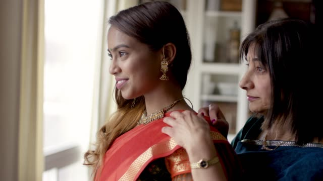 Indian Mother Helping Her Adult Daughter Get Dressed A senior Indian mother is helping her adult daughter with her traditional indian wardrobe. She is wearing a dress and they are smiling and content. sari stock videos & royalty-free footage
