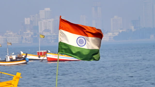 Indian national flag waving in a sea against city skyline video