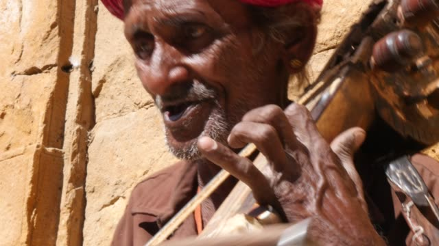 Indian senior plays traditional musical instrument in Jaisalmer Fort, Rajasthan, India video
