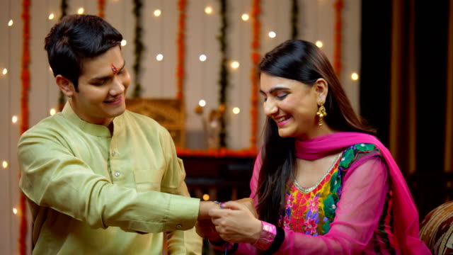 indian sister tying rakhi on her brother's wrist and expressing the love - raksha bandhan - ultra high definition television filmów i materiałów b-roll