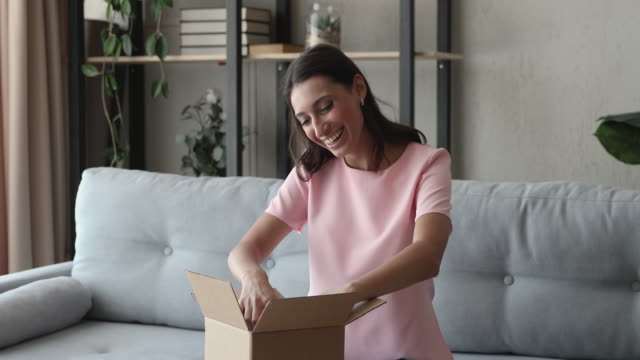 Indian woman open carton box received delivered goods feels satisfied