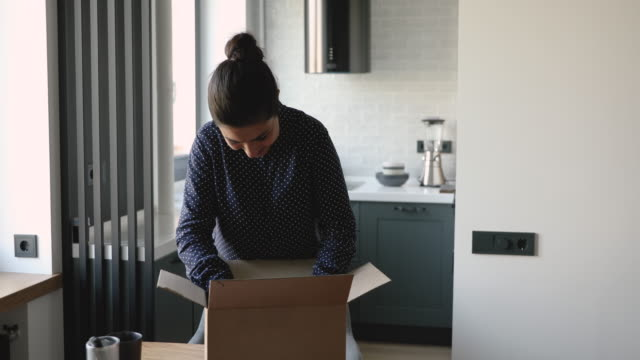 indian woman opens parcel satisfied by goods bought in internet - e mail filmów i materiałów b-roll