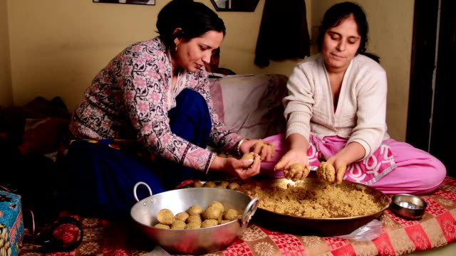 Indian women making sweet dish at home Mid adult women of Indian ethnicity preparing laddu at home. haryana stock videos & royalty-free footage