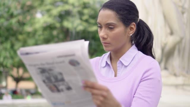 stockvideo's en b-roll-footage met indiase vrouwen lezen van de krant in een stadspark - 30 39 jaar
