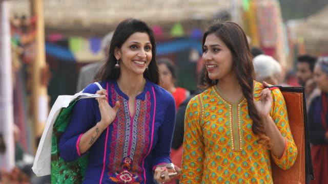 indian women talking on the move at street market - hindus filmów i materiałów b-roll