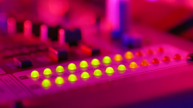 stockvideo's en b-roll-footage met led-indicator niveau signaal van volume op de sound mixing console of dj console op de party in nightclub - geluidsopname apparatuur