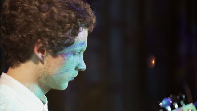 Indie-style curly bass player plays bass guitar in a dark club and bright light illuminates it