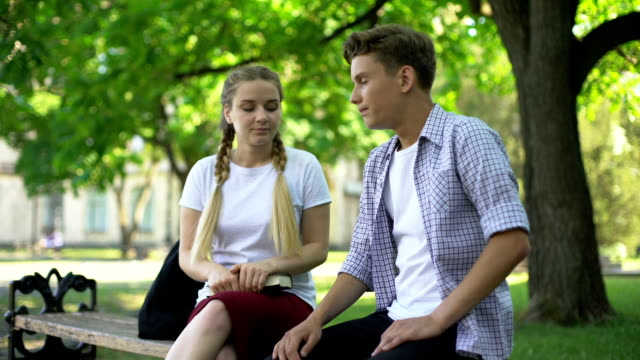 Indifferent teens sitting on bench, bad blind date, wasting time, ignoring