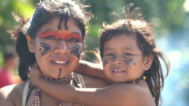 indigenous brazilian young women and her child, portrait from tupi guarani ethnicity - costume tradizionale video stock e b–roll