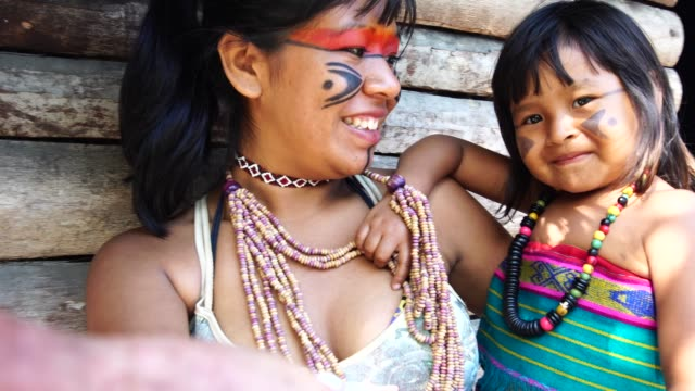 indigenous brazilian young women taking a selfie with her sister from tupi guarani ethnicity - этническая группа стоковые видео и кадры b-roll