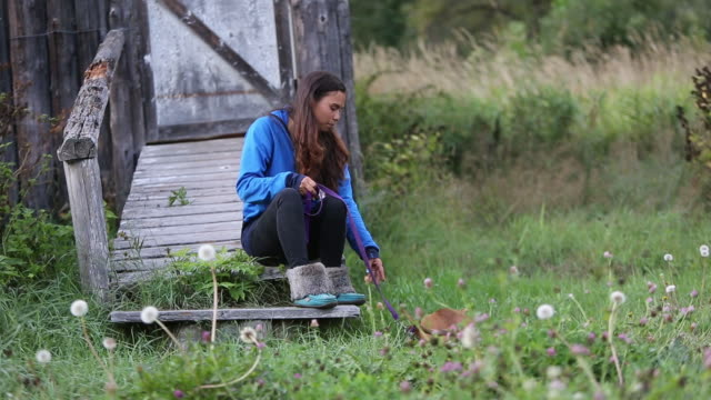 Indigenous Canadian woman playing with her pet dog