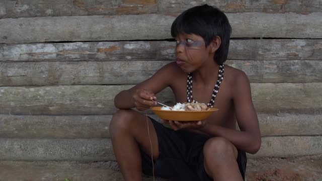 Indigenous Children eating a traditional food in Brazil Indigenous Children eating a traditional food in Brazil hungry stock videos & royalty-free footage