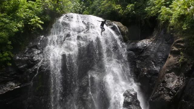 Indigenous Fijian man jumps from Vuadomo Waterfall in Vanua LevuIsland Fiji video