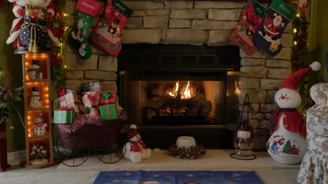 Indoor Christmas Scene with a Fire Place Indoor Christmas Scene with a Mantle and Fire Place Santa Clause and Stockings fireplace stock videos & royalty-free footage