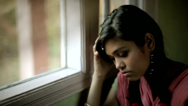 Indoor close-up of sad Asian teenager girl sitting near window. Indoor, panning video in natural light of serene and sad Asian teenager girl with long and black braided hair sitting near window by holding her head in hand and wearing traditional Indian dress (Salwaar Kameez, Dupatta). She is thinking deeply and looking away at something outside window with sadness and blank expression on her face. One person, horizontal composition and selective focus. indian culture stock videos & royalty-free footage