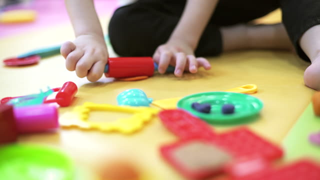 Indoor portrait of young caucasian child playing with play dough focusing on his hand. video