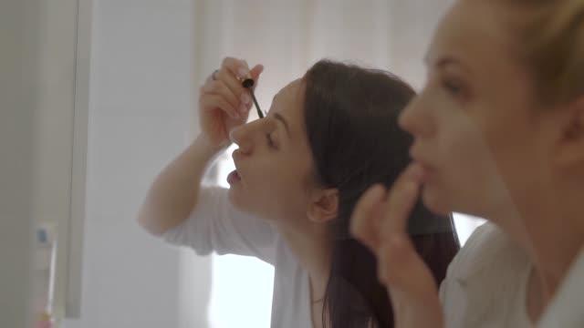 朝鏡の前に立ち、化粧を施す2人の若い女性の屋内ショット - マスカラ点の映像素材/bロール