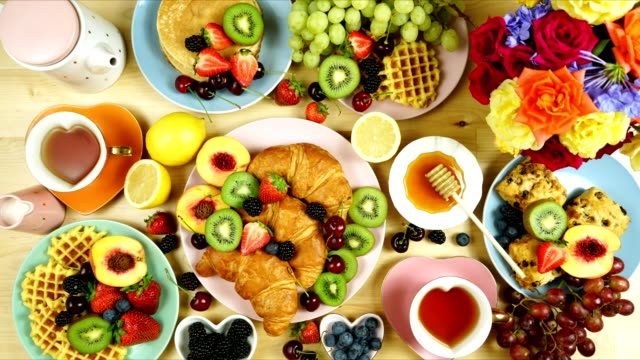 indulgent breakfast flat lay with croissants, pancakes, waffles, and fruit. - cucina francese video stock e b–roll
